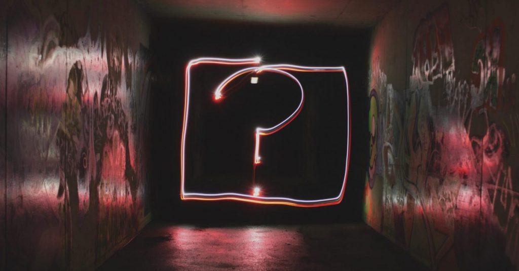 image description: neon questionmark on a black background